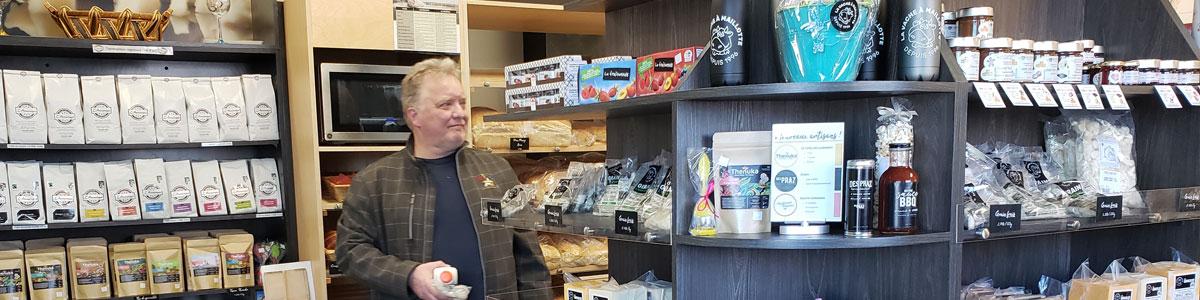 Un homme fait des achats dans la boutique de la fromagerie